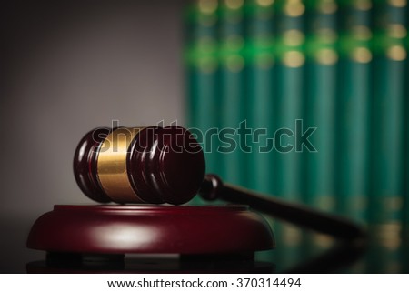 wooden gavel in front of a row of books in studio - stock photo