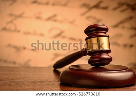 Wooden gavel on a plinth conceptual of justice, punishment , sentencing or an auctioneer standing on a wooden table in front of a blurred handwritten document with copy space