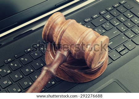 Wooden gavel on laptop computer, cyber law or crime concept - stock photo