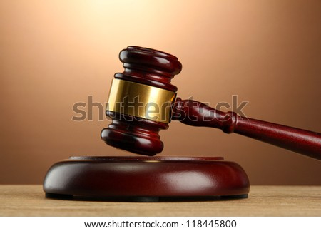 wooden gavel on wooden table, on brown background - stock photo