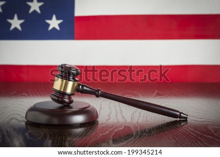 Wooden Gavel Resting on American Flag Reflecting Table. - stock photo