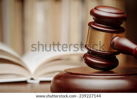Wooden gavel resting on its end on a wooden table in front of an open law book conceptual of a judge, courtroom and judgements - stock photo