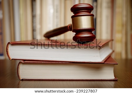 Wooden gavel resting on two large books conceptual of the judiciary, judgements, court and law enforcement