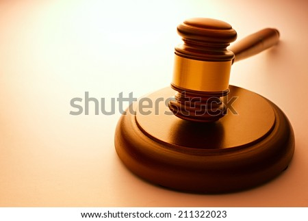 Wooden gavel with a brass band resting on a plinth used by a judge or auctioneer and conceptual of justice and judgements with backlit highlight and copyspace