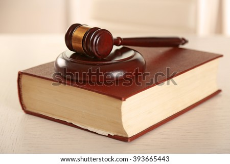 Wooden gavel with book on table closeup