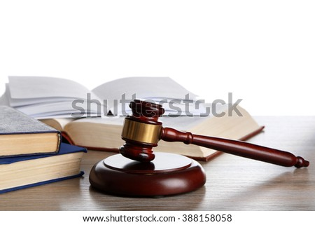Wooden gavel with books on white background