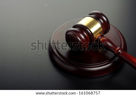 wooden gavel with golden ornament on a black background