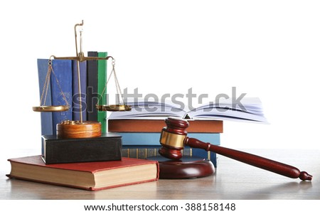Wooden gavel with justice scales and stacks of books on white background - stock photo