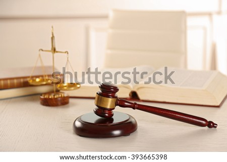 Wooden gavel with open book on table indoors