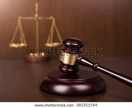 Wooden gavel with scales on wooden table, law concept - stock photo