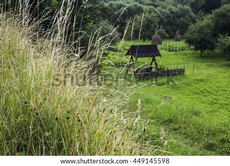 Wooden gazebo in the floodplain of the river against the background of haystacks and trees in the foreground grass Eared - stock photo