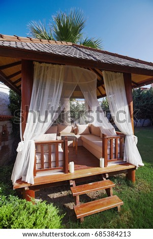 Wooden Gazebo On Green Grass With Soft Sofa And Pillows For Relaxing