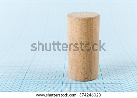 Wooden geometric shape cylinder on graph paper