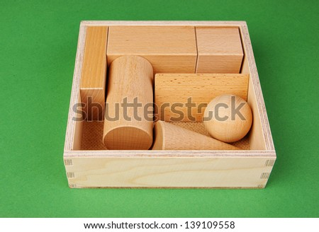 wooden geometric shapes in a box on a green background - stock photo