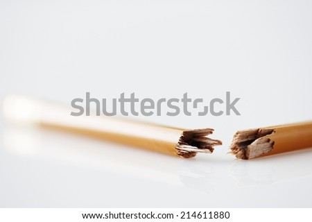 Wooden graphite pencil snapped in half lying on a white surface conceptual of anger, frustration and pressure in the office - stock photo