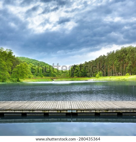 wooden gray pier on lake and landscape of trees and blue sky  - stock photo