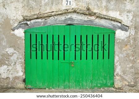 Wooden green door of a boat shelter in Majorca - stock photo