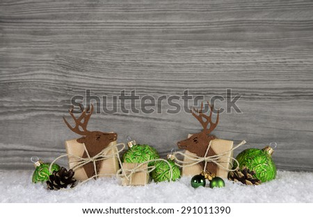 Wooden grey christmas background with reindeer, balls and gifts in green and brown colors. - stock photo