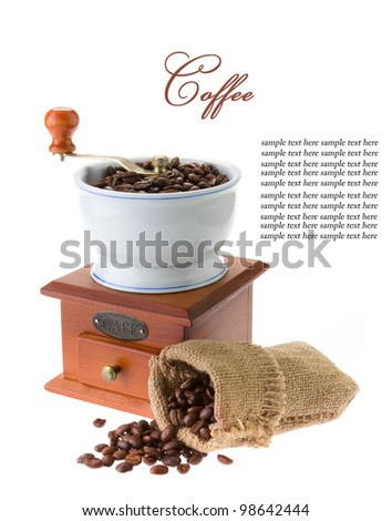Wooden grinder with coffee beans isolated on white background - stock photo