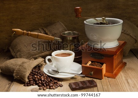 Wooden grinder with coffee beans on the tree with a bag