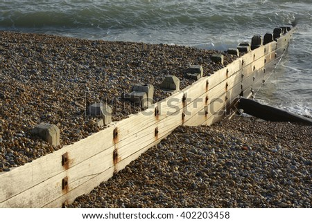 Wooden groyne beach defences on shingle beach at Brighton, East Sussex, England.