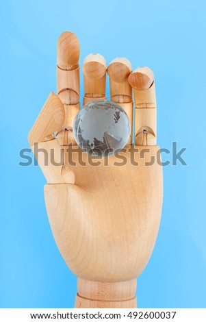 Wooden hand holding small glass globe on white background