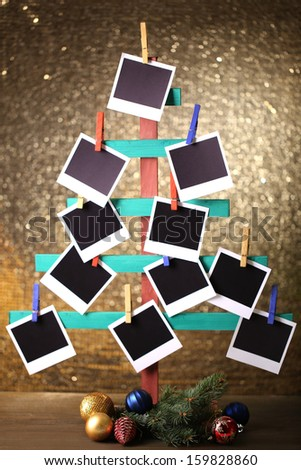 Wooden hand made fir tree with empty photo paper and Christmas decor on shiny background - stock photo