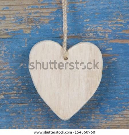 Wooden handmade heart shape against blue wooden surface.  - stock photo