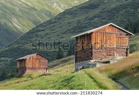 Wooden haylofts on the alpine meadows in Tujetsch valley, Switzerland - stock photo