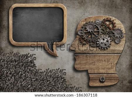 wooden head with speech bubble blackboard - stock photo