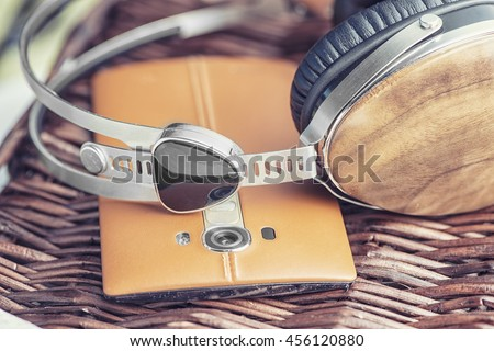 wooden headphones laying on leatter back smart phone