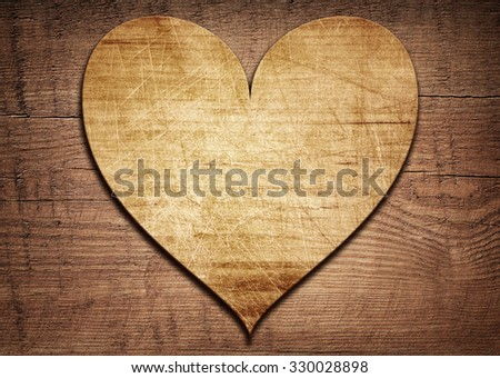 Wooden heart placed on a brown wood board - stock photo