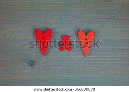 Wooden hearts on clothespins on grey wooden background. Post card for the Valentine. Button love. Wooden buttons. Valentine's Day postcard.