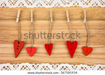 Wooden hearts on clothespins on wooden background with lace. Post card for the Valentine. Button love. Wooden buttons. Valentine's Day postcard. - stock photo