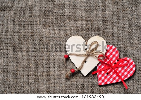 Wooden hearts on fabric background - stock photo