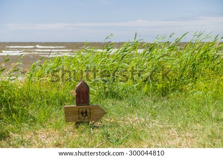 Wooden hiking trail signpost on the seacoast - stock photo