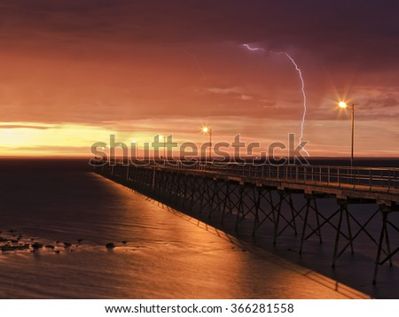 Wooden historic fishing jetty in Ceduna, South Australia, at sunset during heavy rainy storm with lightning