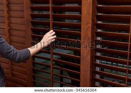 Wooden horizontal blind, Close , women hand - stock photo
