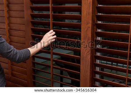 wooden horizontal blind close women hand