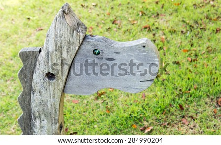 Wooden horse in the playground of small park. - stock photo