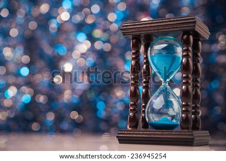 Wooden hourglass clock on abstract background - stock photo