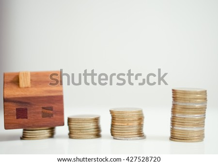 wooden house and stacks of coins standing next/accumulation of funds for a new home.Wooden house block with coins. (finance, property and house loan concept). Project cozy house.Buying a new home.  - stock photo