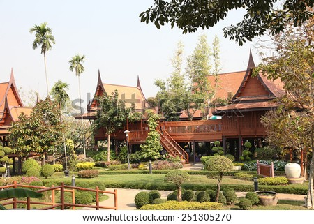 Wooden House high pitched roof elevated central Thailand Landscaped gardens, a large family residence. - stock photo