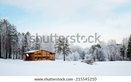 Wooden house in a nature area covered with freshly fallen snow.  - stock photo