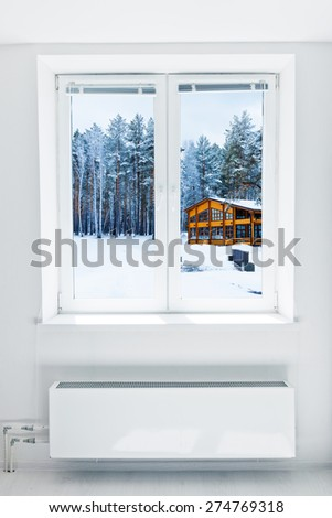 Wooden house in a nature area covered with freshly fallen snow seen through the window - stock photo