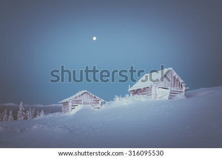 Wooden house in the mountain village. Morning twilight. Winter landscape with snow drifts. The full moon in the clear sky. Color toning. Low contrast