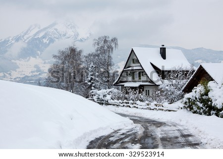 Wooden house in the mountains. Christmas scenery and fresh snow.