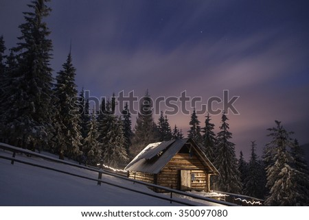 wooden house in winter forest in Crrpathian mountains  , at night - stock photo