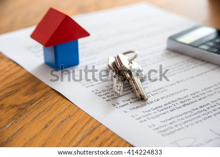 Wooden house miniature and house key lying on contract