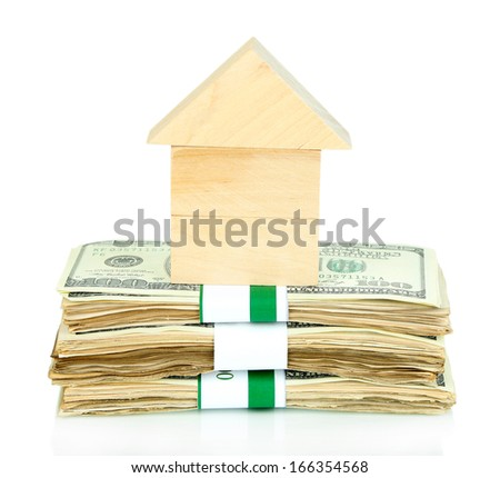 Wooden house on packs of dollars isolated on white